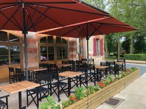 terrasse avec parasol 4 x 4 table 70 x 70 avec pied central et plateau stratifié moulé résistant motif colorado imitation bois de chêne metteur en scène bois noir fabrication italie