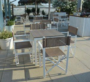 """Table Taverna 4 pieds aluminium blanc 80 cm x 80 cm avec plateau stratifié imitation bois et fauteuils """"metteur en scène"""" avec structure aluminium et toile PVC taupe"""